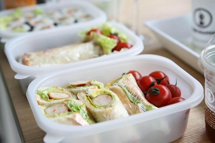 Aud dem Bild sieht man Wraps, Salat und Tomaten in einer Lebensmittel Transportbox