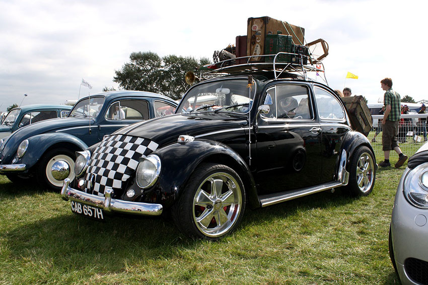 Ein VW Käfer mit vielen Koffern auf dem Dach des Autos