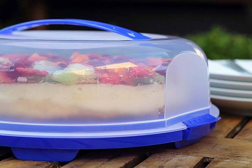 Gezeigt wird eine Lebensmittel Transportbox für Torten. Also eine Tortenbox, die auf einem Tisch steht, blau und durchsichtig ist und mit einem transparenten Deckel vor äußeren EInflüssen geschützt wird.