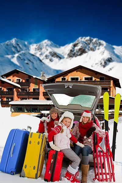 Familie sitzt in offenem Kofferaum mit Gepäck vor Bergkulisse im Winterurlaub